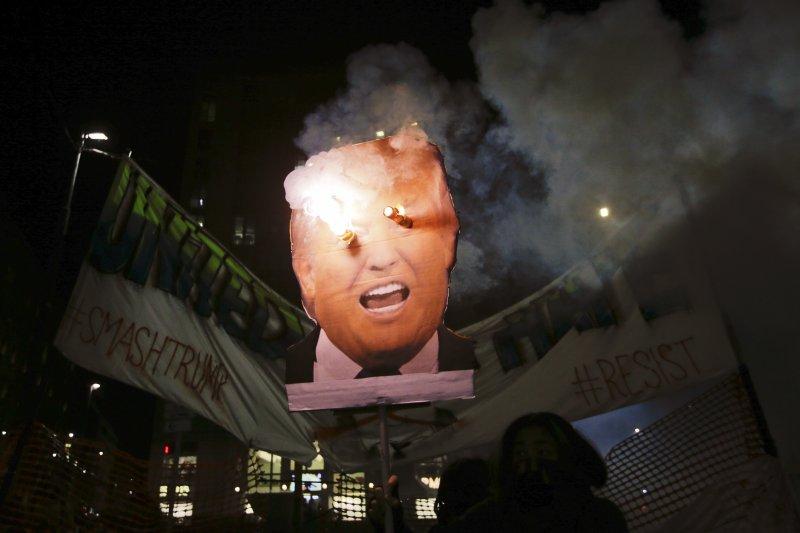 川普20日正式就職,義大利米蘭的抗議民眾高舉嘲弄川普的肖像。(美聯社)