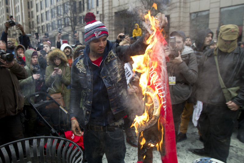 反對川普的抗議者20日在華府街頭焚燒川普的競選T恤。(美聯社)