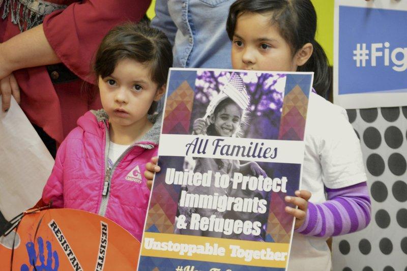 反對川普移民政策的民眾25日在新墨西哥州集會抗議,兩位小朋友手持標語,上頭寫著「所有家庭都應聯合起來保護移民與難民」。(美聯社)