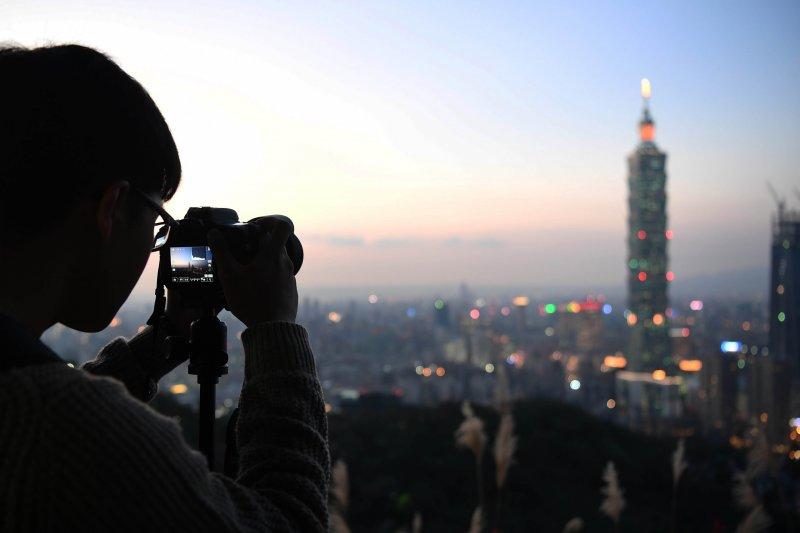 這三年陸客明顯減少,最近北京更進一步暫停陸客來台自由行。圖為陸客在象山取景。(新華社)