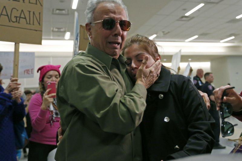 一名被機場扣留數小時的伊朗裔民眾靠在親人身上痛哭。(美聯社)
