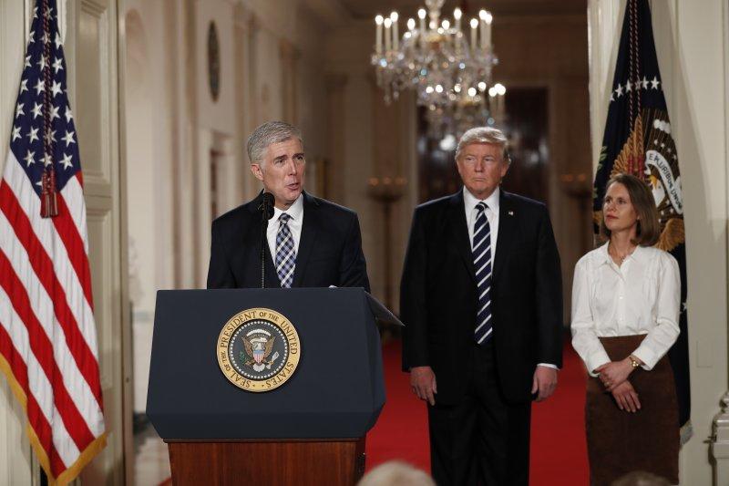 美國總統川普(中)正在聆聽最高法院大法官提名人葛薩奇(左)發表談話(AP)