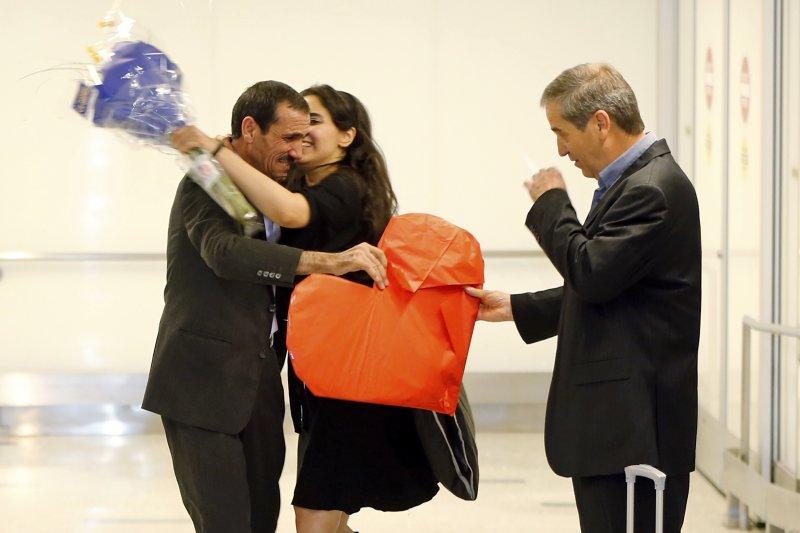伊朗男子瓦耶漢(左)受到前來接機姪女的熱情擁抱(AP)