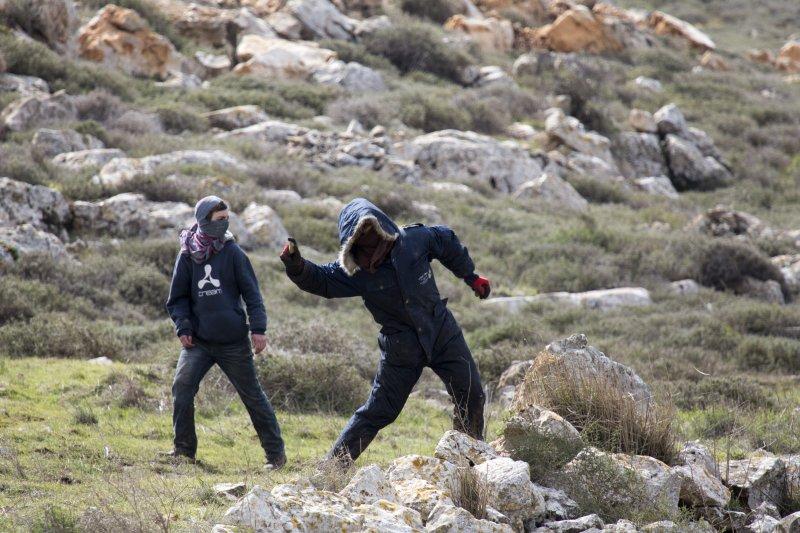 面對優勢警力進駐,被驅趕的以色列民眾也只能在遠處丟擲石塊抗議。(美聯社)