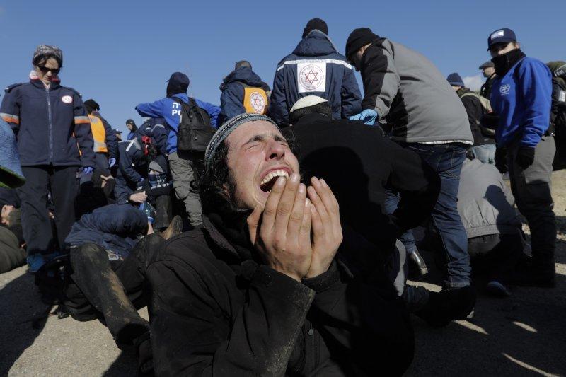 以色列警察2日強勢驅離居住在阿莫納屯墾區的民眾,一位當地居民難過地仰天痛哭。(美聯社)
