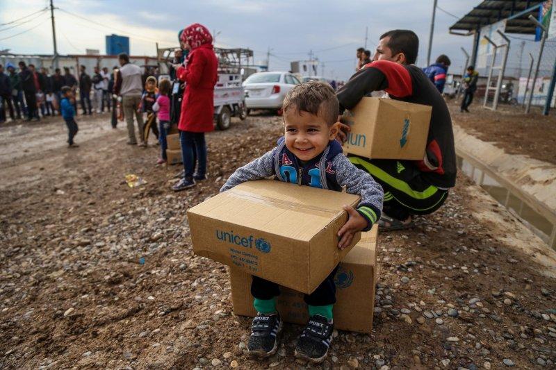 伊拉克一位3歲的孩子在難民營領到聯合國發放的過冬衣物。(聯合國兒童基金會)