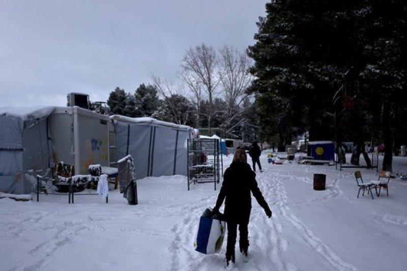 希臘近日下起大雪,雅典附近的瑞佐納(Ritsona)難民營裡,一名難民走在雪地上(AP)