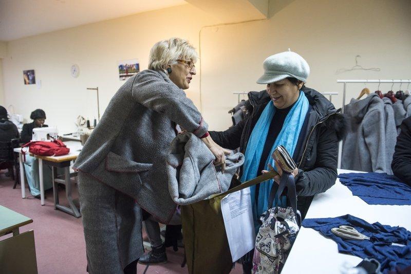 沃施萊格(左)將大衣拿給希臘婦人(AP)
