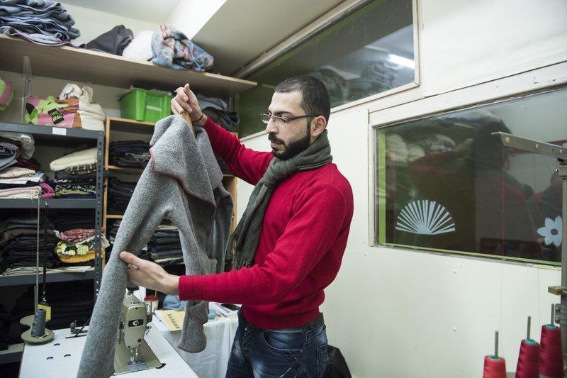 敘利亞難民哈山協助製作大衣(AP)