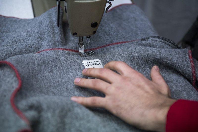 哈山正在製作大衣,大衣標籤寫著「銘記伊多梅尼」(AP)