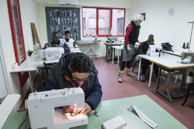一名敘利亞男性難民在「娜歐蜜」的工作坊裡,聚精會神地學習縫紉(AP)