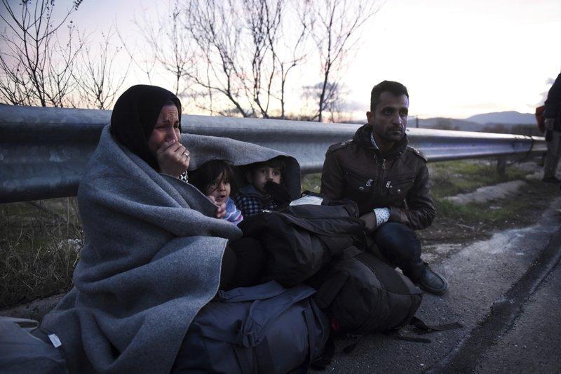 伊多梅尼的一名婦女與孩子裹在毛毯裡,坐在路邊哀哀哭泣(AP)