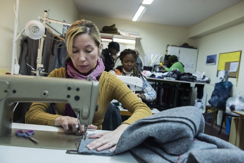 「娜歐蜜」的工作間裡,一名難民正在製作大衣(AP)