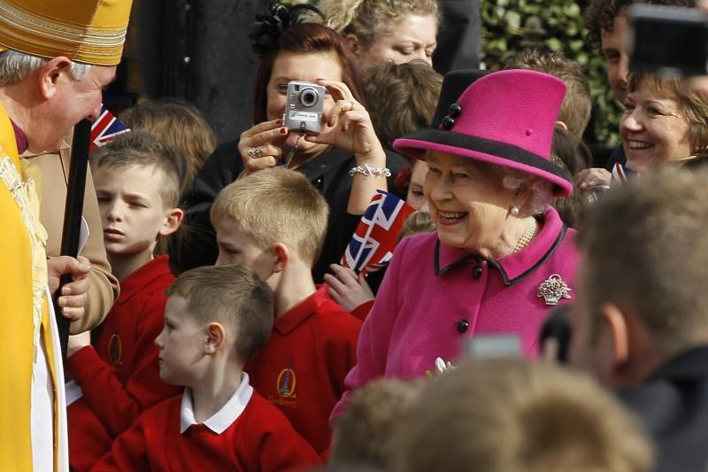 英國女王伊莉莎白二世經常穿著同色系的套裝出席公開場合。(美聯社)