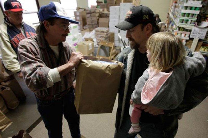 一名剛剛失業的美國男子(右)抱著稚女,收下慈善機構給的免費食物。(AP)