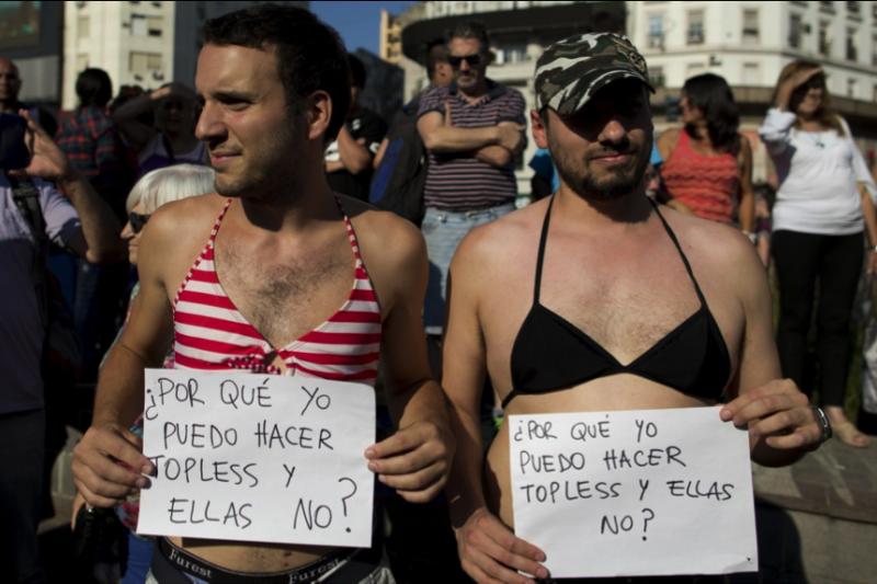 抗議中有兩名男子穿著比基尼,舉著牌子寫道:「為什麼我可以打赤膊她們不行?」。(AP)