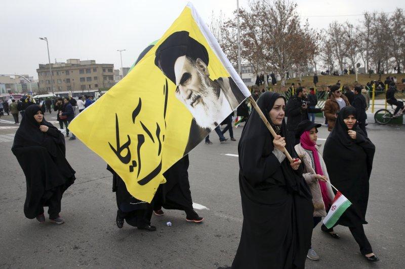 一名伊朗女性扛著印有最高領袖何梅尼(Ruhollah Khomeini)肖像的旗幟,上頭還用波斯文寫著「美國去死」。(美聯社)