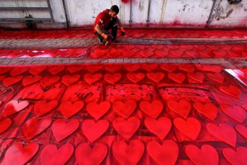 一名伊拉克庫德人在埃爾比勒街頭為情人節慶祝做凖備,他用油漆噴槍為心形圖案上紅色。(圖取自BBC中文網)