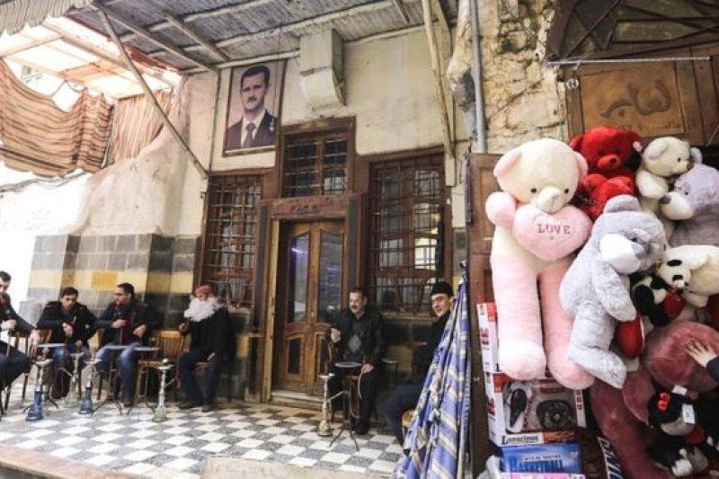 敘利亞首都大馬士革舊城區一家餐廳入口掛著阿塞德總統的頭像,與旁邊的情人節禮品互相映照。(圖取自BBC中文網)