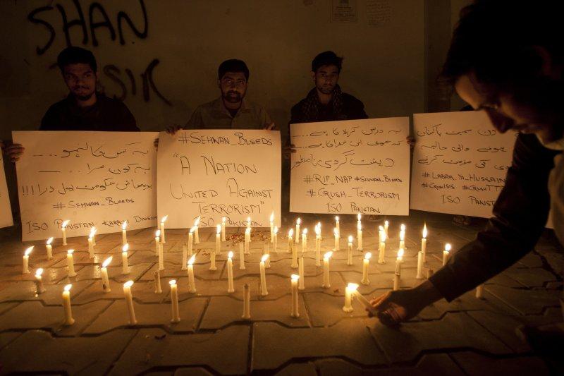 巴基斯坦的大學生為恐怖攻擊的死難者點起蠟燭悼念。(美聯社)