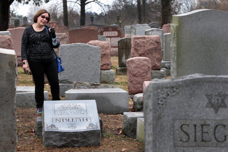 望著被推倒的祖先墓碑,這名女子傷心不已(AP)