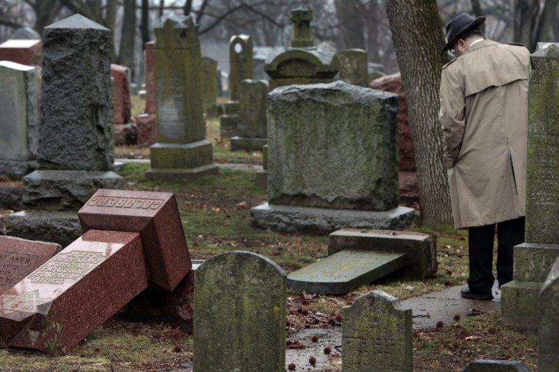 一名男子沈重望著被推倒的墓碑(AP)