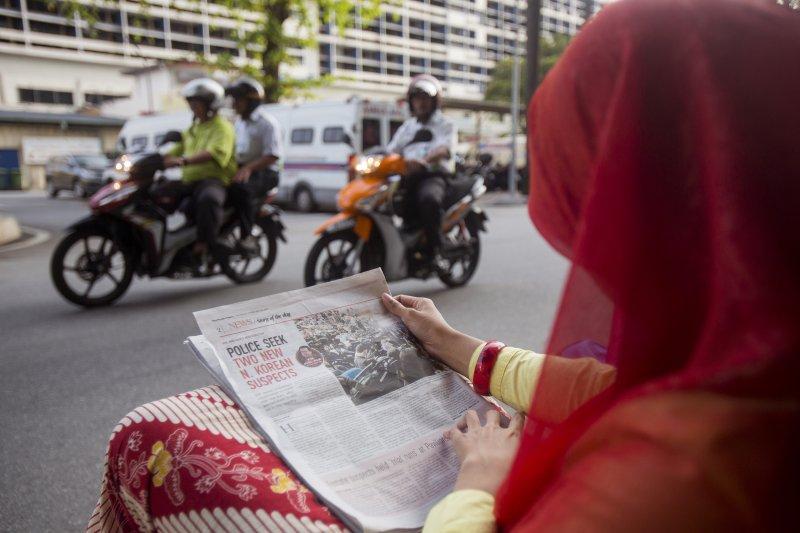 金正男遇刺已成馬來西亞的焦點新聞,一名馬國女性在街頭閱讀相關報導。(美聯社)
