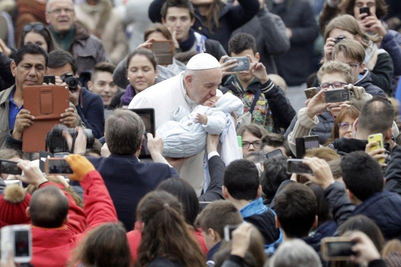 教宗方濟各22日親吻一名沉睡的嬰兒(AP)