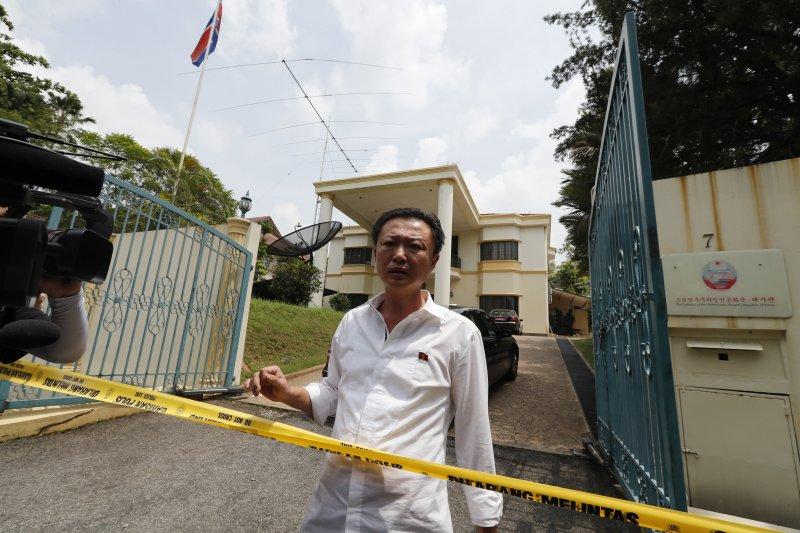 馬來西亞警方7日在北韓大使館外拉起封鎖線,一名北韓使館的工作人員出來詢問是否能夠外出。(美聯社)
