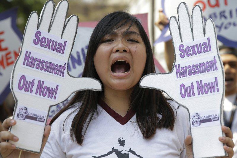 菲律賓女性走上街頭,高舉「性騷擾滾開」標語,喚起社會對女性性騷擾的問題。(美聯社)