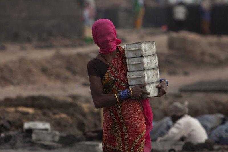 印度一位女性正在工地搬運磚塊。她用薄紗遮住臉龐,以免沙塵入眼。(美聯社)