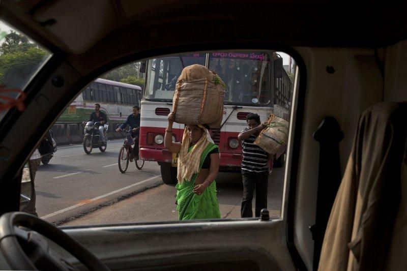 印度海德拉巴德街上一位女性,用頭頂著一籮筐的蔬菜走路。(美聯社)