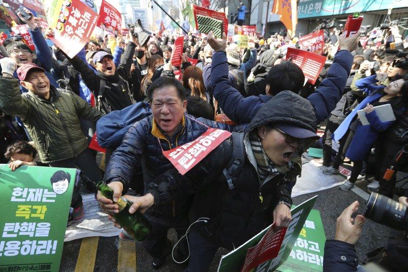 南韓憲法法院10日宣判朴槿惠總統彈劾案,反朴民眾開香檳慶祝(AP)