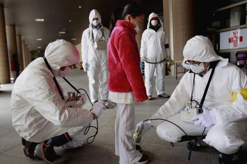 2011年3月24日,一位年輕的被疏散者正在接受輻射檢測。(美聯社)