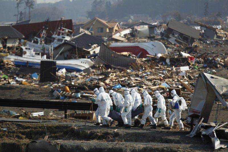 2011年4月15日,福島的搜救人員正在搬運一具海嘯遇難者的屍體。(美聯社)