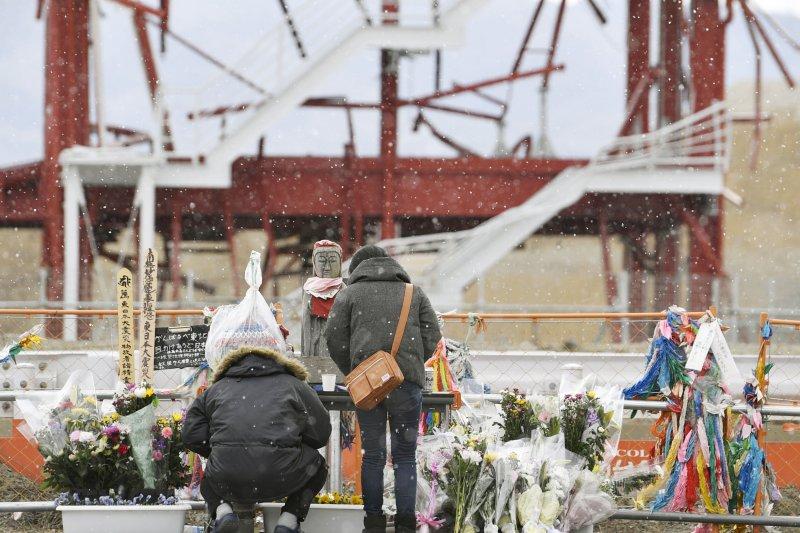 2017年3月11日,311大震災的罹難者家屬在一處災難遺址前獻花致意。(美聯社)