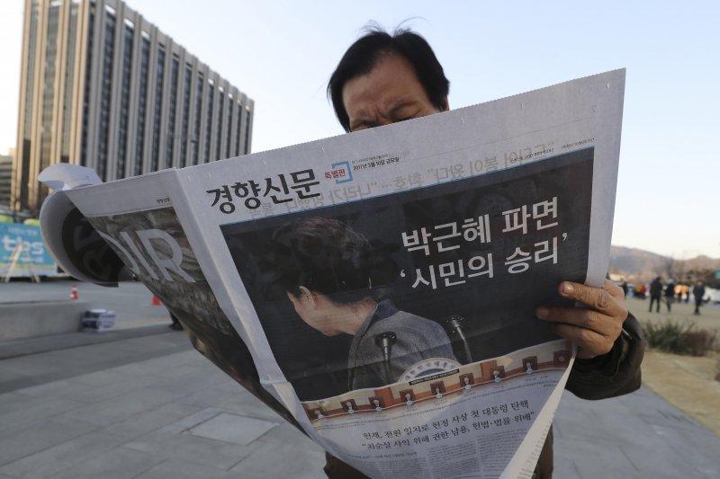 一名南韓民眾正在首爾街頭閱讀朴槿惠遭到罷免解職的號外。(美聯社)