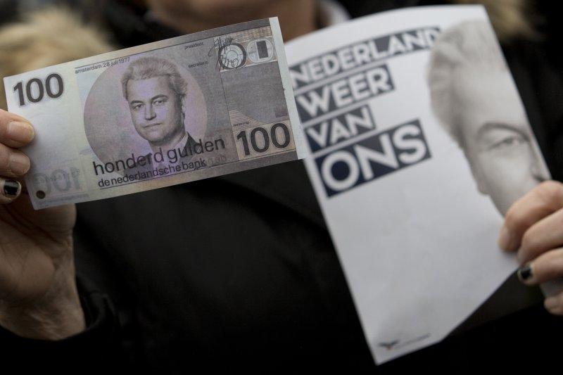 支持者將威爾德斯印成百元鈔票,手上的宣傳單寫著「荷蘭是我們的!」(美聯社)