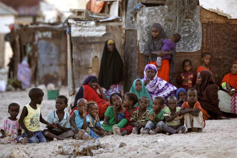 索馬利亞沿海的村莊裡,許多婦孺聚集在滿是塵土的街道上。(美聯社)