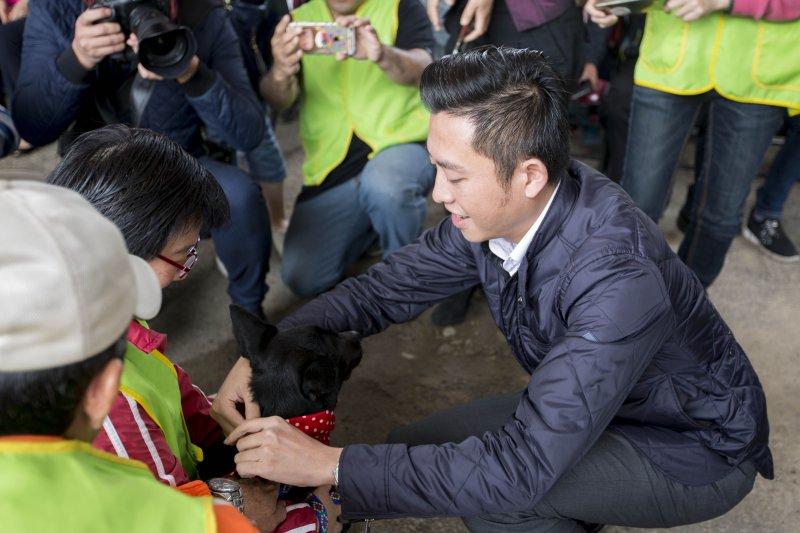 新竹市市長林智堅為流浪狗榜上印有牠們名字的紅色領巾,希望他們都只是園區內的「暫時房客」。(新竹市政府提供)