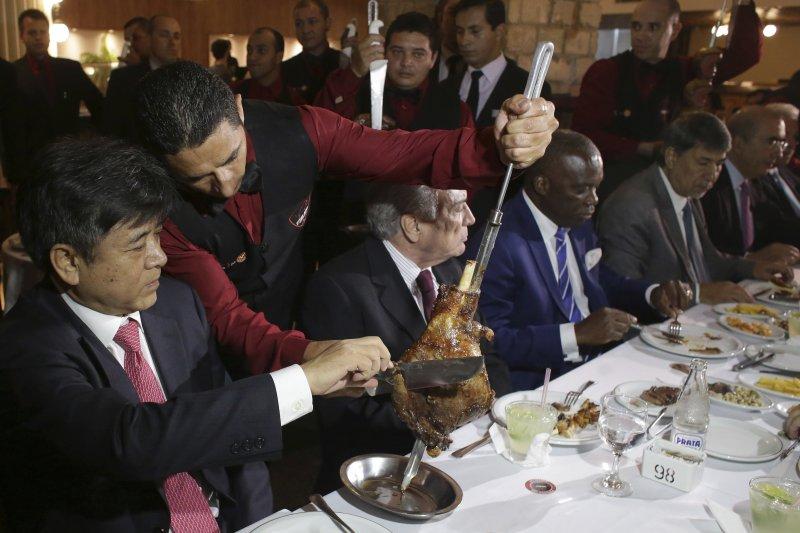 巴西打貪爆出臭肉門事件,總統特梅爾(左2)宴請各國大使吃烤肉消除疑慮,圖為中國駐巴西大使李金章(左1)吃烤肉(AP)