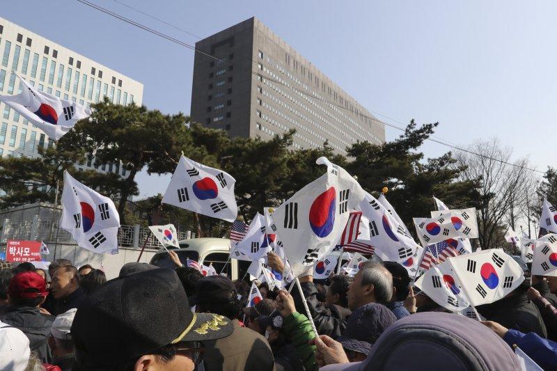朴槿惠的支持者在中央地方檢察廳外揮舞韓國國旗。(美聯社)