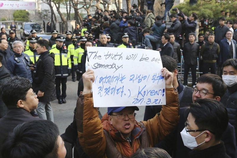朴槿惠支持者在三成洞的朴宅外高舉標語:真相有一天會水落石出。(美聯社)