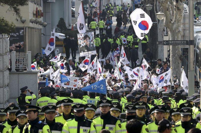 南韓前總統朴槿惠21日前往檢察廳應訊,支持朴槿惠的民眾在檢察廳外揮舞太極旗為她加油。(美聯社)