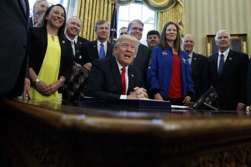 川普在眾多議員與幕僚環繞之下簽署這項法案。(美聯社)