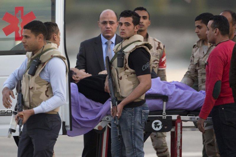 埃及前獨裁者穆巴拉克在維安人員護送下進入救護車。(美聯社)