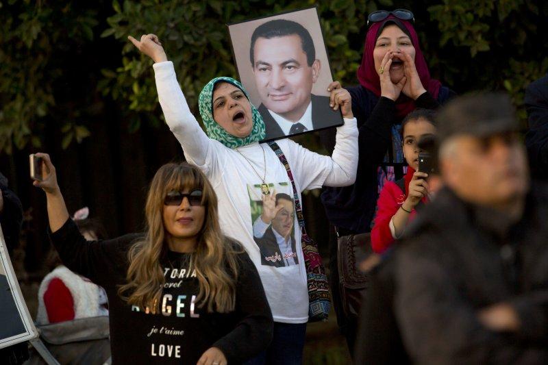 少數穆巴拉克的支持者在法院外高舉其照片。(美聯社)