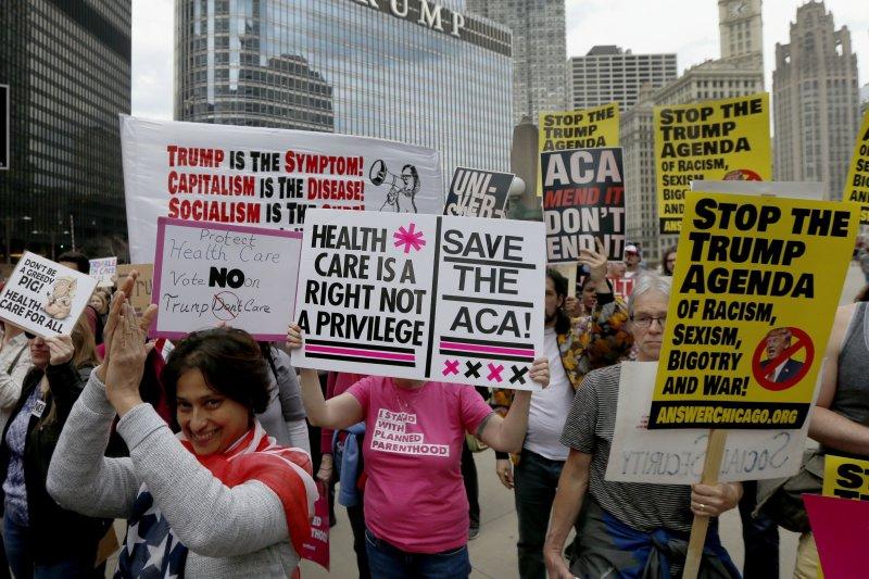 芝加哥民眾24日走上街頭抗議川普廢除「歐巴馬健保」,結果傳來撤案消息後,群眾鼓掌歡呼。(美聯社)