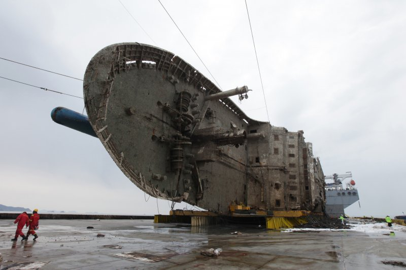 2014年4月沉沒、奪走304條人命的南韓渡輪「世越號」26日被抬到半潛船上,準備運往木浦新港(AP)