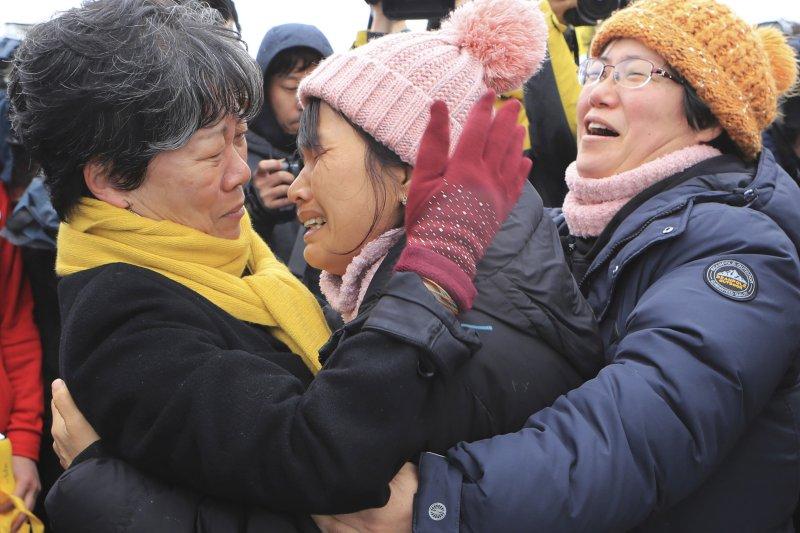 2014年4月沉沒、奪走304條人命的南韓渡輪「世越號」26日被抬到半潛船上,準備運往木浦新港,罹難者家屬至今傷心欲絕(AP)